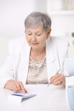 Senior woman sitting at desk using calculator. Stock Photo - 7347654