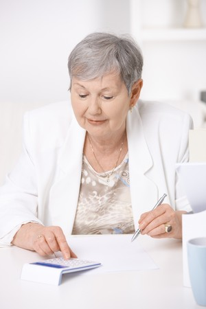Senior woman sitting at desk using calculator. Stock Photo - 7347654