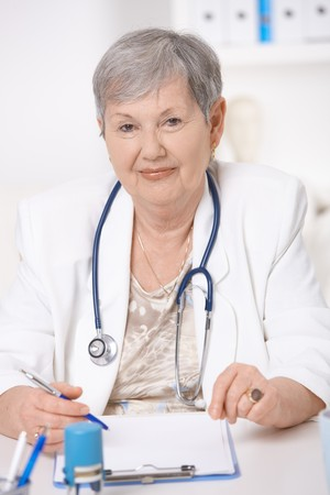 Senior female doctor, working at desk, looking at camera. Stock Photo - 7347661