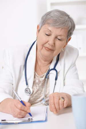 Senior female doctor, working at desk, writing notes. photo