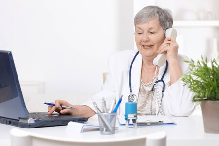hablando por telefono: Senior Femenino m�dico, trabajando en mostrador, equipo port�til.