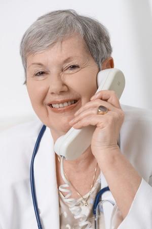 Happy senior female doctor, talking on phone, smiling. Stock Photo - 7347741