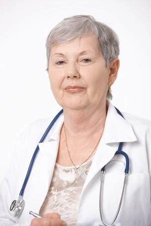 unsmiling: Portrait of senior female doctor, wearing white coat and stethoscope.