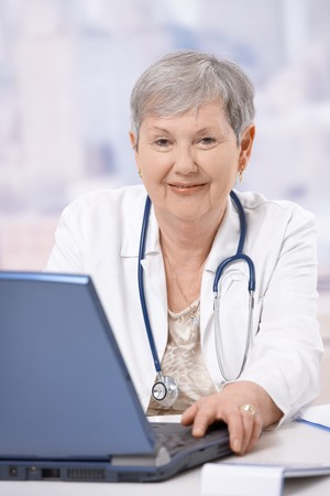 Portrait of happy senior doctor, sitting at desk, looking at camera, smiling. Stock Photo - 7347728