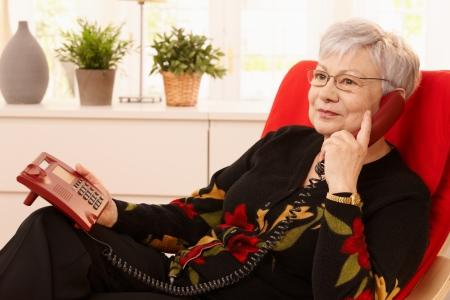 Pensioner woman using landline phone sitting in armchair in living room.