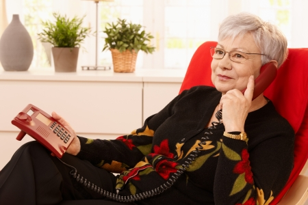 pensioners: Pensioner woman using landline phone sitting in armchair in living room.