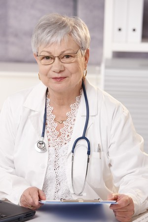 Senior doctor in office holding clipboard, smiling at camera. photo