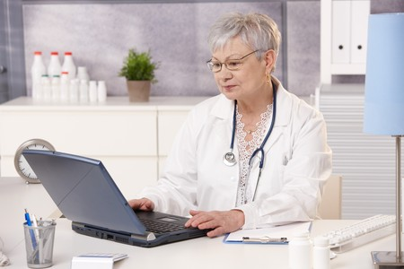 Senior doctor working at desk with computer in office. photo