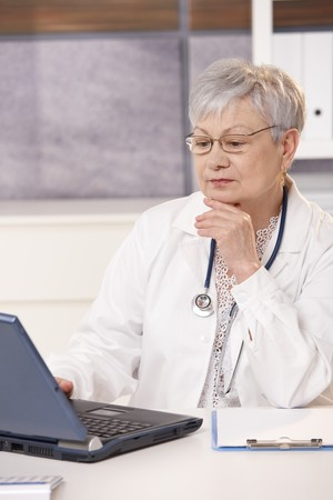 Senior doctor looking at computer screen, thinking. Stock Photo - 7386817