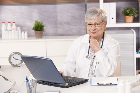 Portrait of senior doctor in office, sitting at desk, looking at camera, smiling. photo