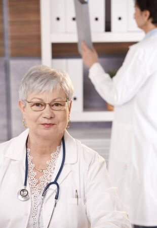Portrait of senior doctor in office smiling at camera, assistant in background. photo