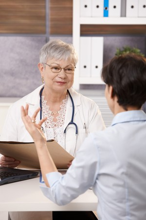 Patient gesturing to smiling doctor in bright office. photo