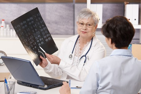 color consultant: Senior doctor showing x-ray results to patient in office.