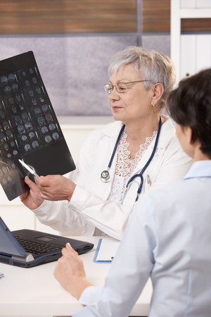 Doctor explaining patient scan results in bright office. photo