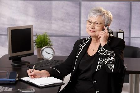 taking note: Businesswoman Senior utilizzando il cellulare al banco, prendendo note, sorridente.  Archivio Fotografico