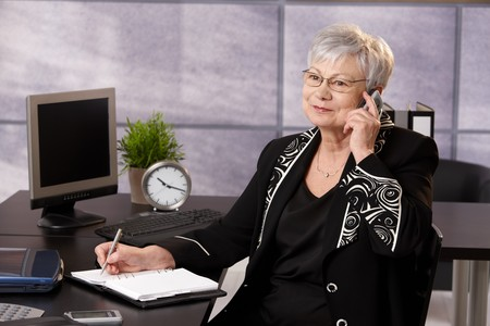 one senior adult woman: Senior empresaria mediante tel�fono celular en mostrador, tomando notas, sonriendo.
