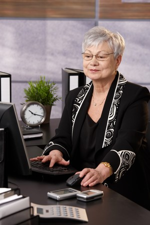 Portrait of senior businesswoman working with computer at desk in office. photo
