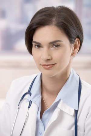 Closeup portrait of attractive young female doctor looking at camera, smiling. photo