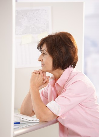 older women: Senior woman sitting in office, thinking, smiling.