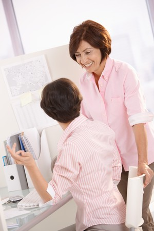 Happy female coworkers chatting at office desk, senior woman smiling. photo