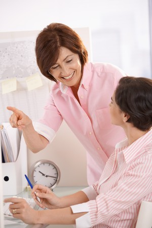 Senior office worker teaching coworker in office, smiling, pointing. Stock Photo - 7390418