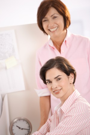 Portrait of two businesswomen smiling at camera in office. photo