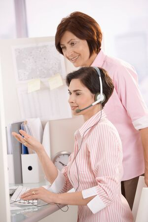 Customer care operator working at desk with supervisor, smiling. photo