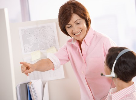 Smiling senior supervisor helping customer care operator, pointing. Stock Photo - 7390251