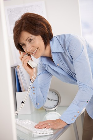 Smiling senior businesswoman on landline phone call at office desk. Stock Photo - 7386781