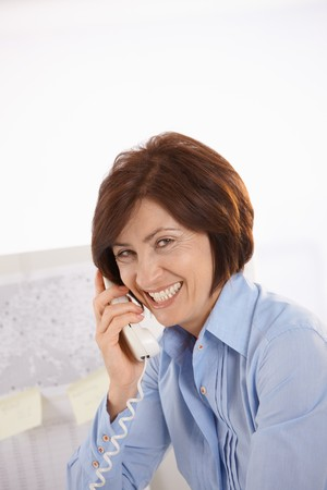 Portrait of senior office worker talking on landline phone, laughing. photo