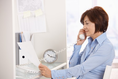 Senior businesswoman listening to landline phone call reading paper handheld. photo