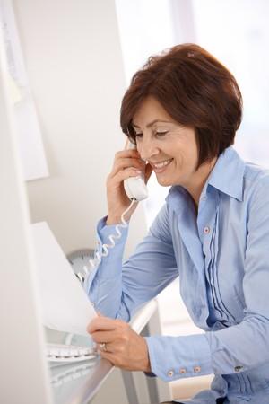 Smiling senior businesswoman talking on landline phone, looking at paper handheld . photo