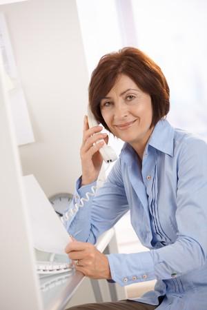 one senior adult woman: Portrait of senior office worker sitting at desk, using landline phone, holding paper.