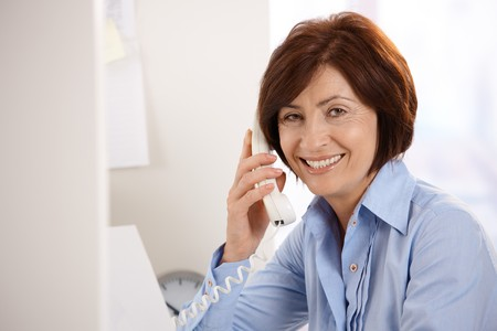 only mature women: Portrait of smiling senior office worker sitting at desk, using landline phone, looking at camera.