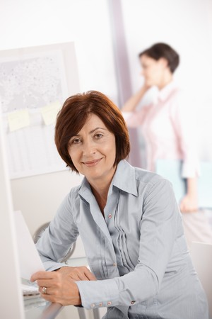 Portrait of confident mature businesswoman smiling at camera, colleague in background. photo