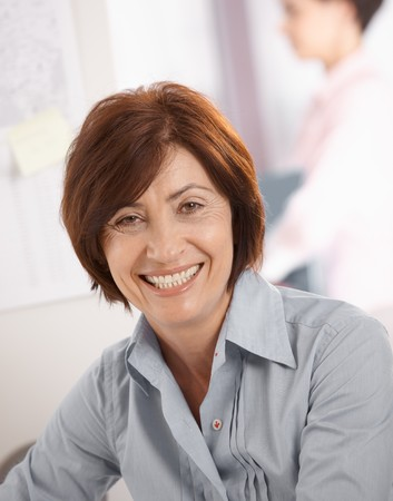 senior business: Portrait of senior businesswoman smiling at camera, coworker in background.