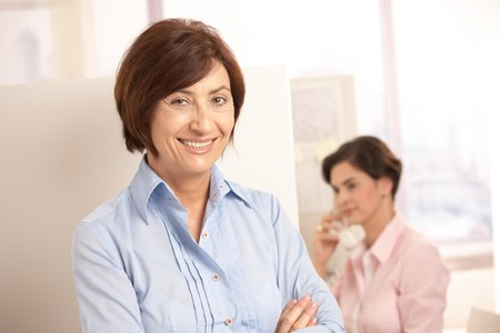 Senior professional woman smiling at camera, assistant using landline phone in background. photo