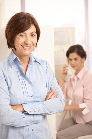 Portrait of mature office worker smiling at camera, colleague talking on phone in background. photo