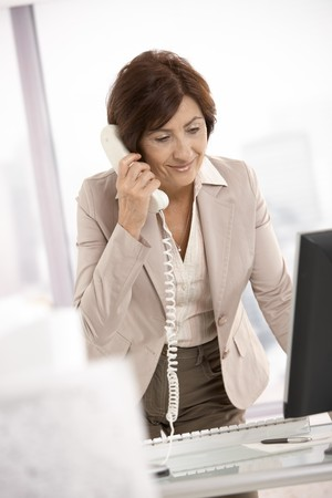 mujeres ancianas: Sonriente empresaria senior, hablando por tel�fono de l�nea fija en mostrador, sonriendo.  Foto de archivo