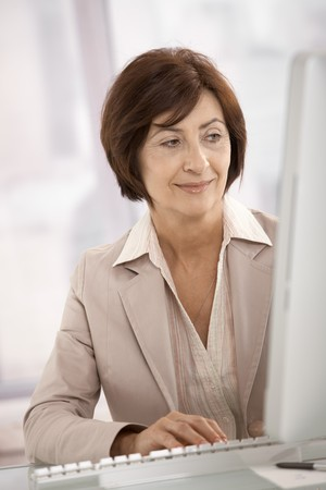 only senior women: Smiling businesswoman using desktop computer in office.