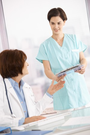 Smiling assistant handing over clipboard to doctor sitting at desk. Stock Photo - 7390240