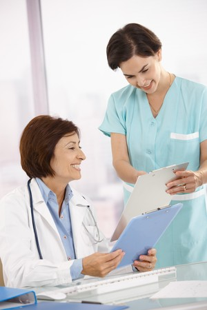 co worker: Smiling medical expertise sitting at desk, doing paperwork with assistant.