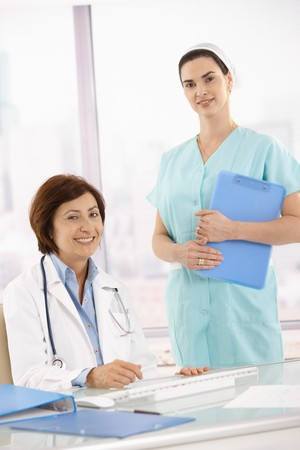 Portrait of senior medical doctor with assistant, smiling at camera. Stock Photo - 7390237