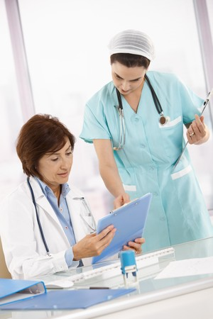 analysing: Nurse and doctor working in office, analysing diagnosis together.