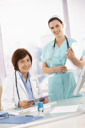 Portrait d'un médecin et une infirmière au travail, tenant le presse-papiers, regardant la caméra en souriant. Banque d'images - 7390239