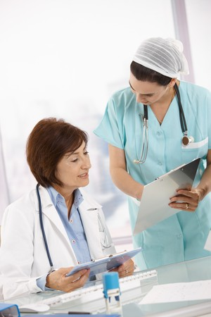 Nurse and senior doctor analysing diagnosis together at office desk. photo