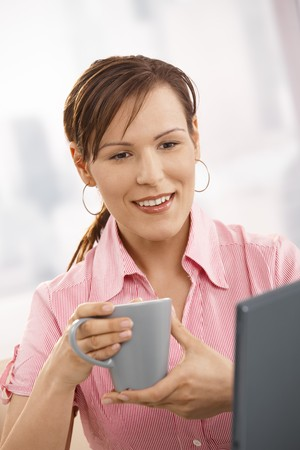 Office worker drinking tea at desk, looking at laptop screen, smiling. Stock Photo - 7390596