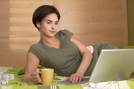 Portrait of smiling woman having coffee and using laptop lying on bed in morning. photo