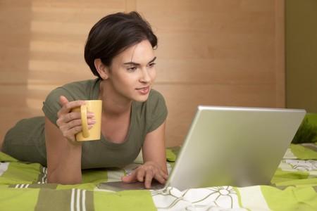 Woman lying on bed using laptop computer holding coffee mug. photo