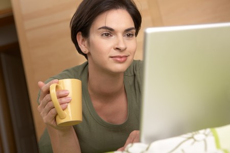 nighty: Woman looking at laptop screen smiling, holding coffee mug at home. Stock Photo